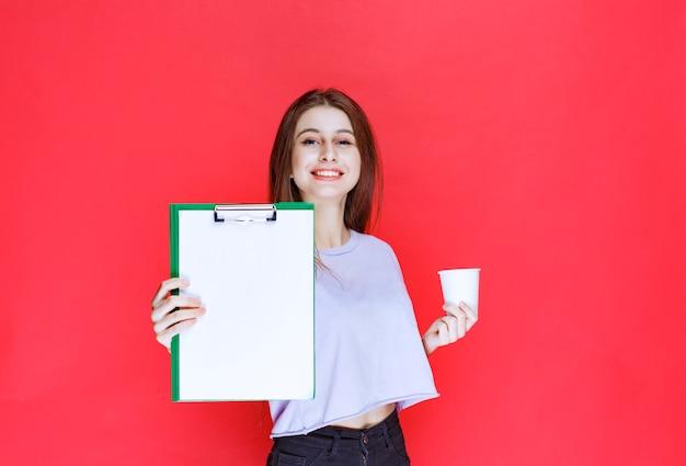 Jonge vrouw met rapport blad en een kopje drank.