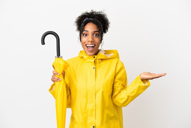Jonge vrouw met regenbestendige jas en paraplu geïsoleerd op een witte achtergrond met geschokte gezichtsuitdrukking