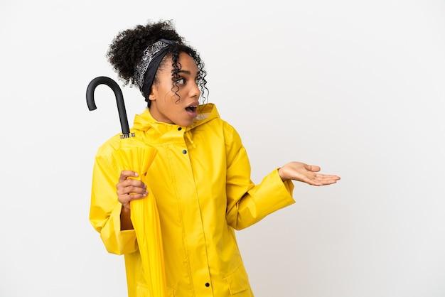Jonge vrouw met regenbestendige jas en paraplu geïsoleerd op een witte achtergrond met verrassingsuitdrukking terwijl ze opzij kijkt