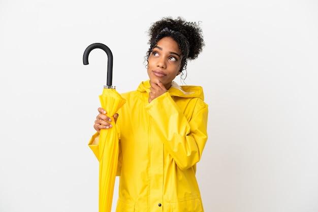 Jonge vrouw met regendichte jas en paraplu geïsoleerd op een witte achtergrond en opzoeken