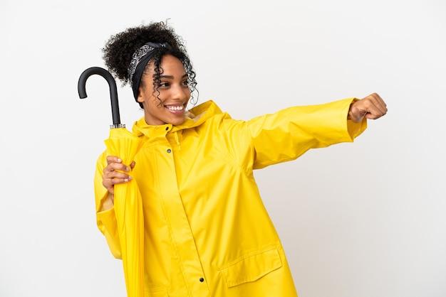 Jonge vrouw met regendichte jas en paraplu geïsoleerd op een witte achtergrond met een duim omhoog gebaar