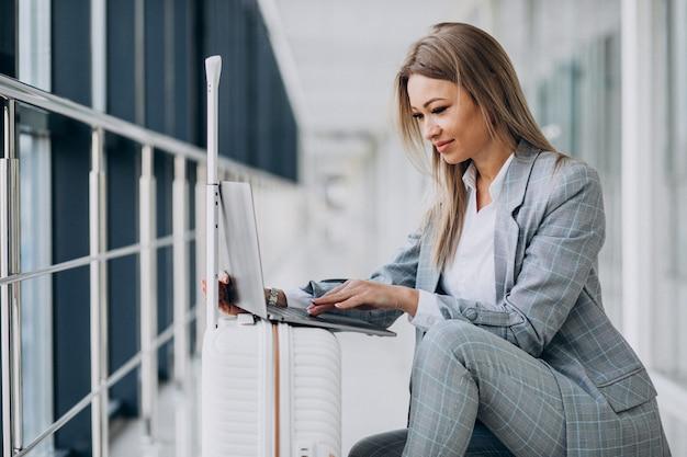 Jonge vrouw met reistas, die een vlucht op laptop in luchthaven boeken