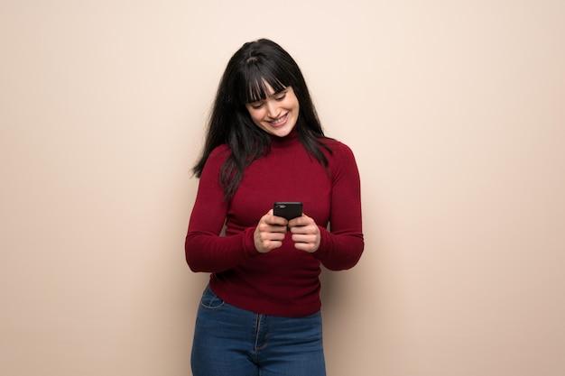 Jonge vrouw met rode col die een bericht met mobiel verzendt