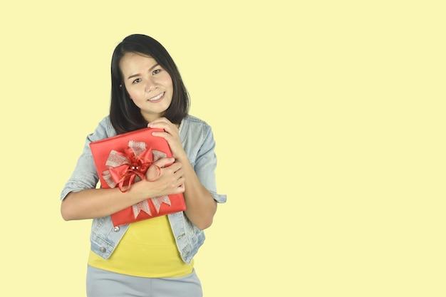 Jonge vrouw met rode geschenkdoos aanwezig voor verjaardag valentijn dag kerstmis nieuwjaar concept