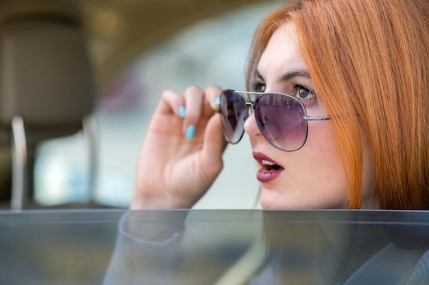 Jonge vrouw met rode haar en zonglazen die met de auto reizen. passagier kijkt uit de achterruit van een taxi in een stad.