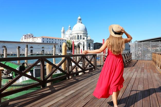 Jonge vrouw met rode jurk en hoed loopt in venetië, italië