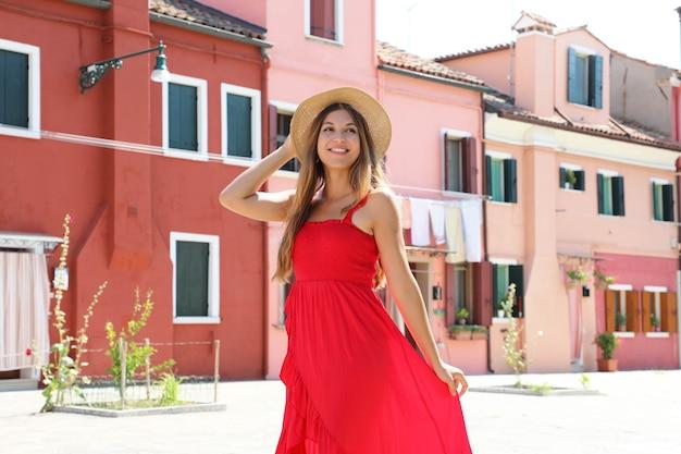 Jonge vrouw met rode lange jurk wandelen in burano, venetië, italië