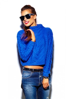 Jonge vrouw met rode lippen en blauwe trui in zonnebril
