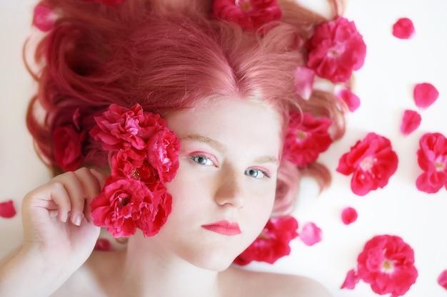 Jonge vrouw met rode rozen op witte ondergrond