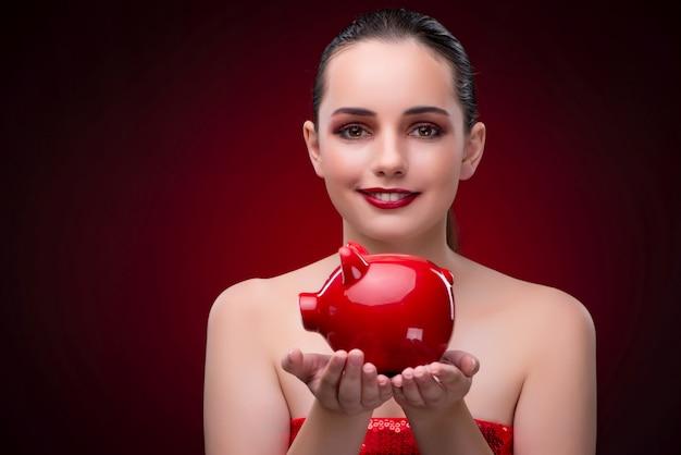 Jonge vrouw met rode spaarpot