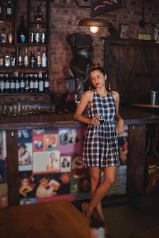 Jonge vrouw met rode wijn in pub