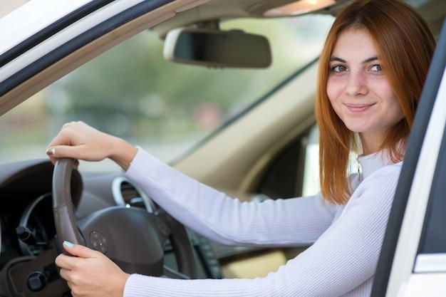 Jonge vrouw met rood haar dat een auto drijft.