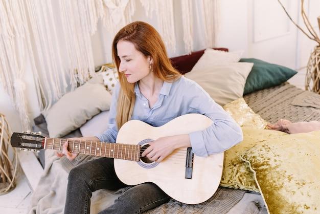 Jonge vrouw met rood haar die thuis muziek studeren.