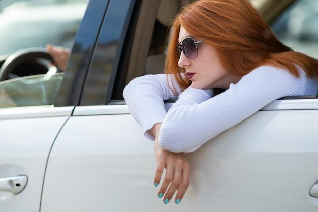 Jonge vrouw met rood haar en zonnebril reizen met de auto. passagier kijkt uit de achterruit van een taxi in een stad.
