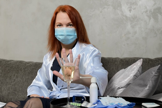 Jonge vrouw met rood haar in medisch masker toont gebaar van afwijzing van een glas champagne.