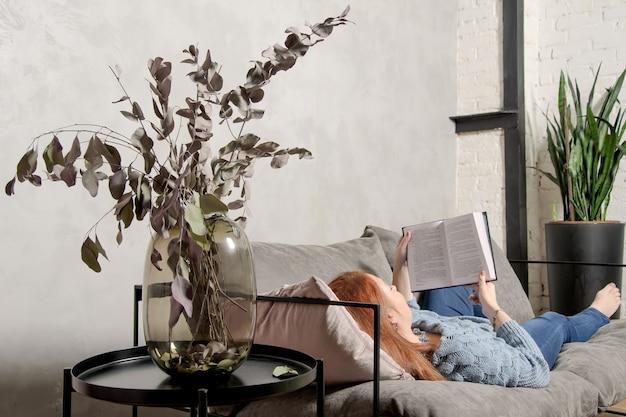 Jonge vrouw met rood haar ligt op de bank en leest boek. rustig recreatiewoning met boek in gezellig interieur.