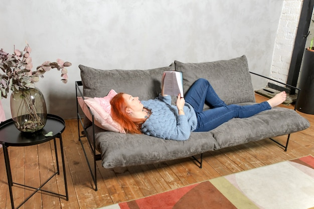 Jonge vrouw met rood haar ligt op de bank en leest boek. rustige vrije tijd thuis met boek in gezellig interieur.