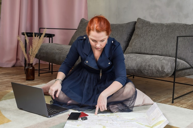 Jonge vrouw met rood haar zit op de vloer in haar appartement en is van plan reis met laptop en papieren kaart