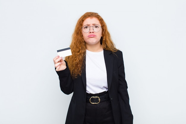 Jonge vrouw met rood hoofd, verdrietig en zeurderig met een ongelukkige blik, huilend met een negatieve en gefrustreerde houding over witte muur
