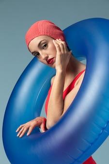 Jonge vrouw met rood zwempak en een zwemmende ring