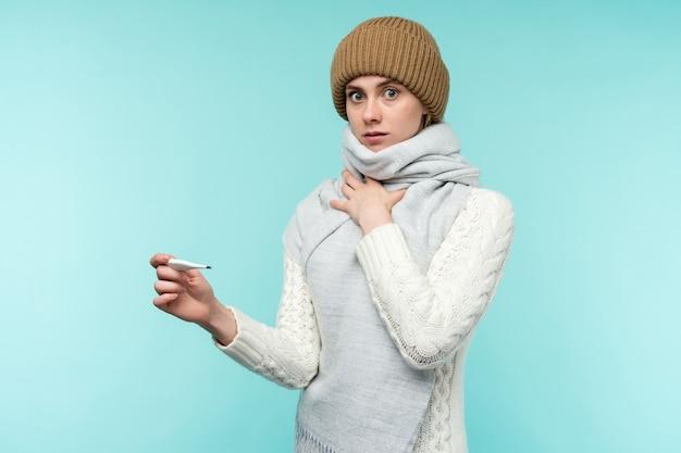 Jonge vrouw met rookgasafvoer thermometer tegen blauwe achtergrond mooie dame is ziek met een hoge temperatuur en keelpijn geïsoleerde close-up koude griep concept