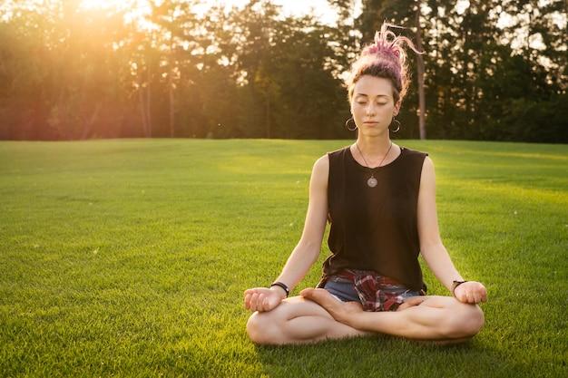 Jonge vrouw met roze dreadlocks die buiten yoga-oefeningen doet en mediteert in het park bij zonsondergang. lotuspositie