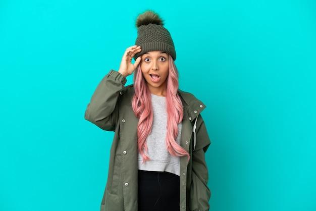 Jonge vrouw met roze haar die een regenbestendige jas draagt die op een blauwe achtergrond is geïsoleerd, heeft iets gerealiseerd en is van plan de oplossing te vinden