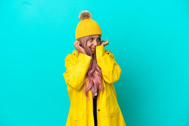 Jonge vrouw met roze haar die een regenbestendige jas draagt, geïsoleerd op een blauwe achtergrond, gefrustreerd en oren bedekt