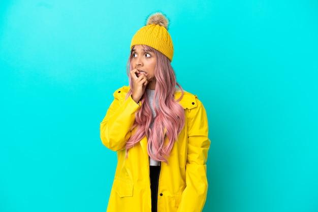 Jonge vrouw met roze haar die een regenbestendige jas draagt, geïsoleerd op een blauwe achtergrond, is een beetje nerveus