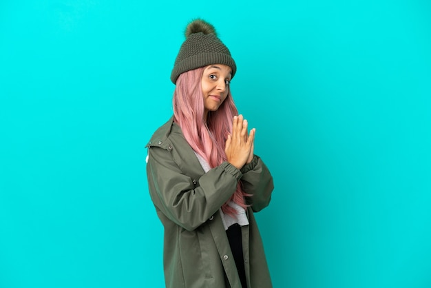 Jonge vrouw met roze haar die een regendichte jas draagt, geïsoleerd op een blauwe achtergrond, iets intrigeert