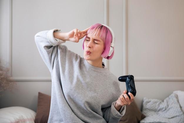 Jonge vrouw met roze haar die een videogame speelt
