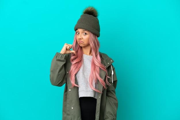 Jonge vrouw met roze haar, gekleed in een regenbestendige jas geïsoleerd op blauwe achtergrond trots en zelfvoldaan