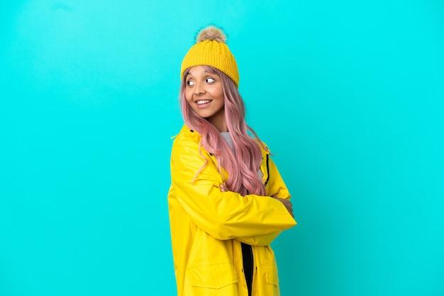Jonge vrouw met roze haar, gekleed in een regenbestendige jas geïsoleerd op een blauwe achtergrond, opzij kijkend en glimlachend