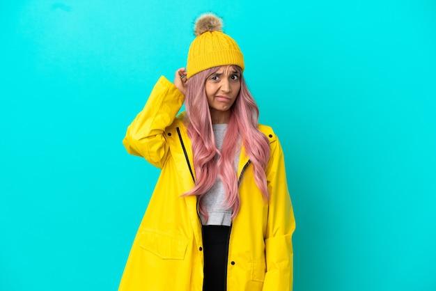 Jonge vrouw met roze haar, gekleed in een regenbestendige jas geïsoleerd op een blauwe achtergrond, twijfels