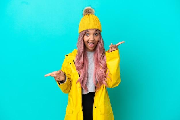 Jonge vrouw met roze haar, gekleed in een regenbestendige jas geïsoleerd op een blauwe achtergrond, wijzende vinger naar de zijkanten en gelukkig