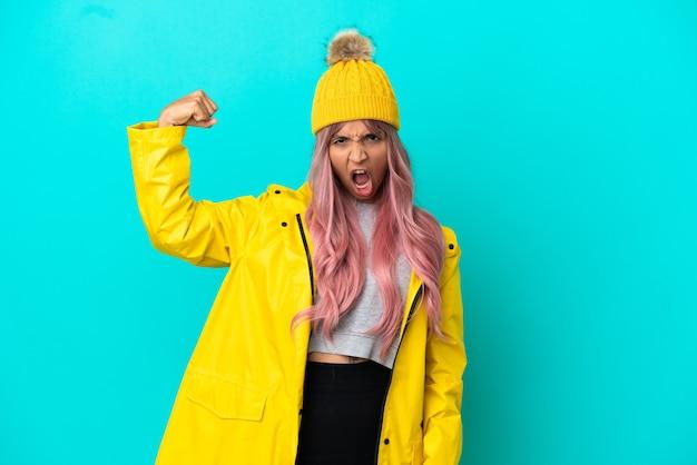 Jonge vrouw met roze haar met een regenbestendige jas geïsoleerd op een blauwe achtergrond die een sterk gebaar doet