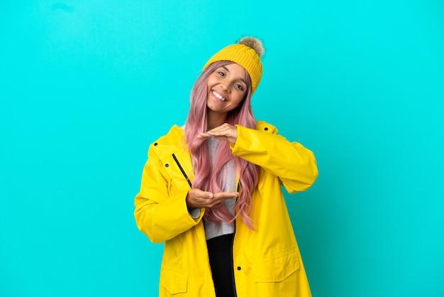 Jonge vrouw met roze haar met een regenbestendige jas geïsoleerd op een blauwe achtergrond met copyspace denkbeeldig op de palm om een advertentie in te voegen