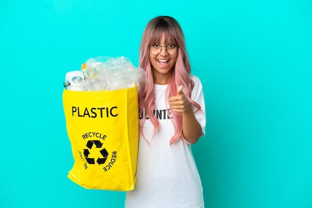 Jonge vrouw met roze haar met een zak vol plastic flessen om te recyclen geïsoleerd op blauwe achtergrond met duimen omhoog omdat er iets goeds is gebeurd