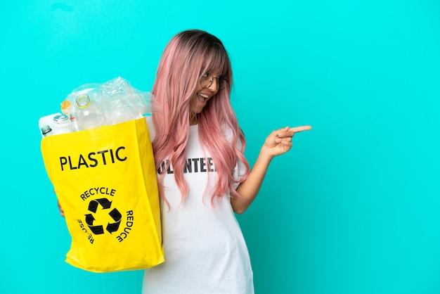 Jonge vrouw met roze haar met een zak vol plastic flessen om te recyclen geïsoleerd op blauwe achtergrond wijzende vinger naar de zijkant en presenteren van een product