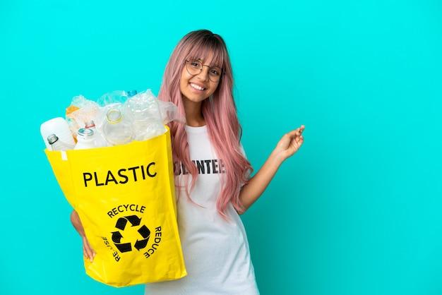 Jonge vrouw met roze haar met een zak vol plastic flessen om te recyclen geïsoleerd op een blauwe achtergrond die naar achteren wijst