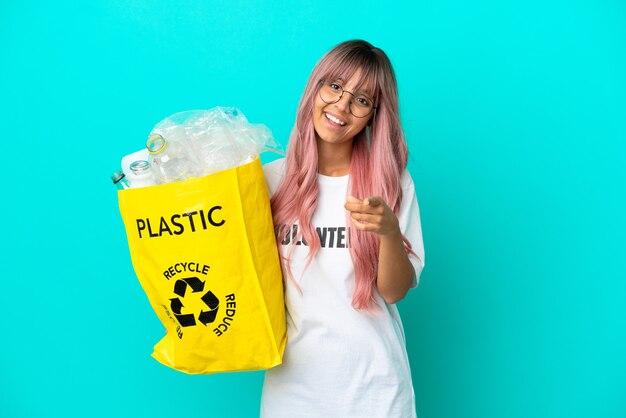 Jonge vrouw met roze haar met een zak vol plastic flessen om te recyclen geïsoleerd op een blauwe achtergrond die naar voren wijst met een gelukkige uitdrukking