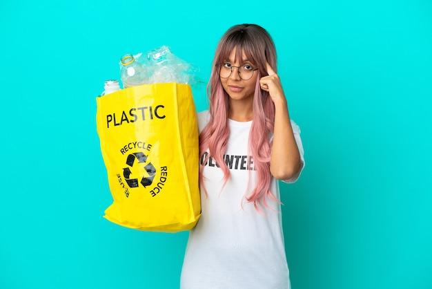 Jonge vrouw met roze haar met een zak vol plastic flessen om te recyclen geïsoleerd op een blauwe achtergrond en denkt aan een idee