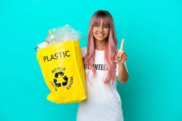 Jonge vrouw met roze haar met een zak vol plastic flessen om te recyclen, geïsoleerd op een blauwe achtergrond en een vinger op te tillen