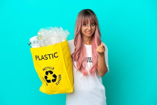 Jonge vrouw met roze haar met een zak vol plastic flessen om te recyclen, geïsoleerd op een blauwe achtergrond, geld gebaar maken