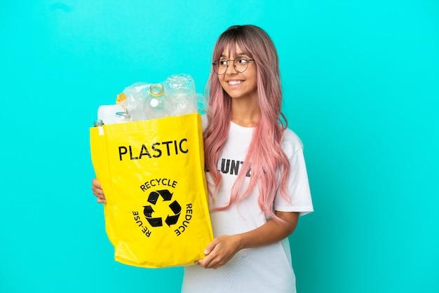 Jonge vrouw met roze haar met een zak vol plastic flessen om te recyclen geïsoleerd op een blauwe achtergrond op zoek naar de zijkant