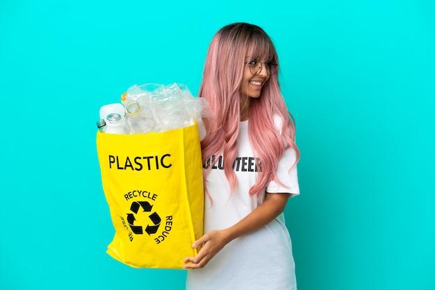 Jonge vrouw met roze haar met een zak vol plastic flessen om te recyclen geïsoleerd op een blauwe achtergrond, opzij kijkend en glimlachend