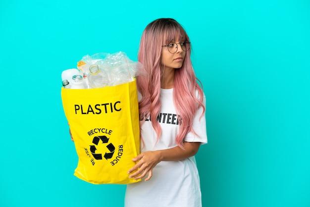 Jonge vrouw met roze haar met een zak vol plastic flessen om te recyclen, geïsoleerd op een blauwe achtergrond, opzij kijkend