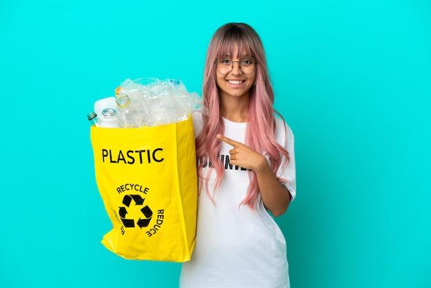 Jonge vrouw met roze haar met een zak vol plastic flessen om te recyclen geïsoleerd op een blauwe achtergrond, wijzend naar de zijkant om een product te presenteren