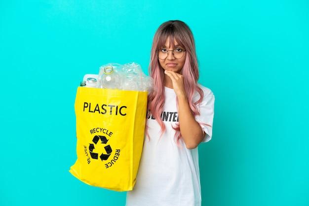 Jonge vrouw met roze haar met een zak vol plastic flessen om te recyclen geïsoleerd op een blauwe achtergrond
