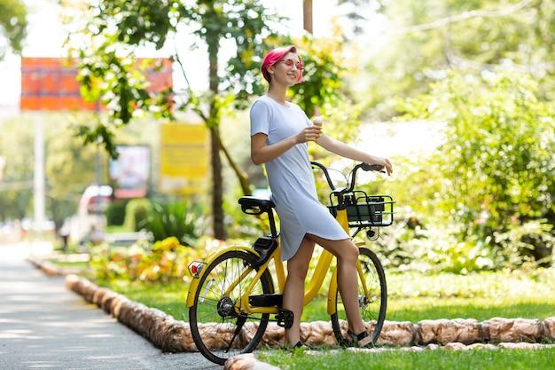 Jonge vrouw met roze haren loopt in het park met een fiets die ijs eet in de zomer. milieu-transportmiddel
